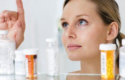 девушка выбирает таблетки
